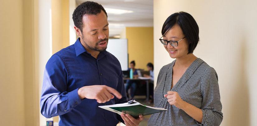 USF Faculty members reviewing paperwork.